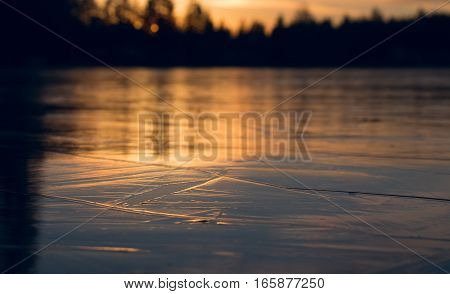 Beautiful ice sheet structure frozen lake at sunset in wintertime. Shallow depth of field.
