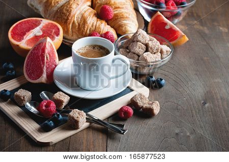 Coffee and croissants with raspberries and fruits for breakfast. Toned image selective focus