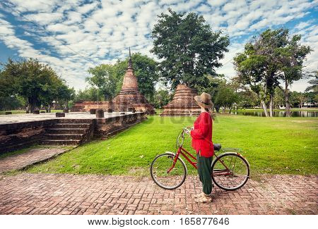 Woman With Bicycle Near Ruins In Thailand