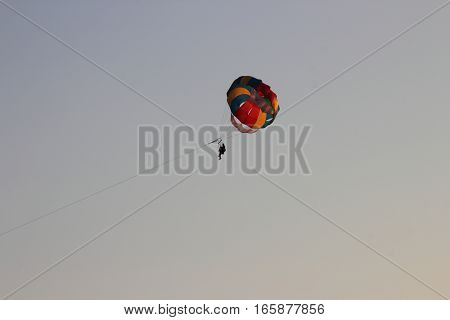 Flight couple on a parachute behind a boat in the sky