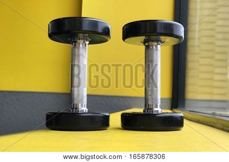 dumbbells in the gym on yellow background