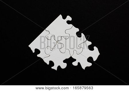 Five blank puzzle pieces on black background