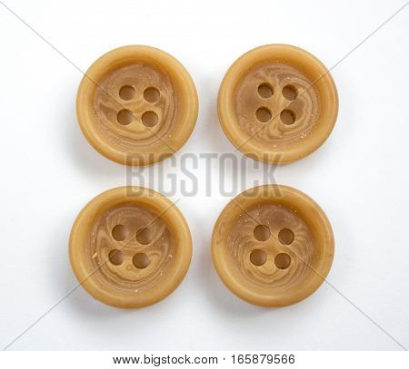 Four Beige Plastic Buttons Isolated On White