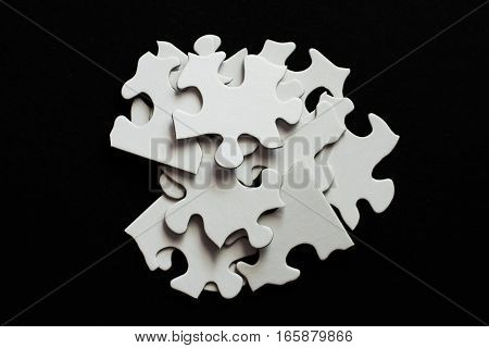 Pile Of Blank Puzzle Pieces On Black Background