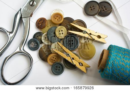 Pile Of Buttons With Sewing Materials And Clothes Pins Isolated On White