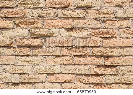 Salmon coloured rough grunge brick pattern on wall