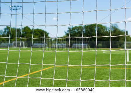 Looking through soccer net on sports field closeup