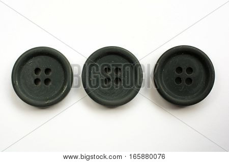 Three Black Plastic Buttons Isolated On White