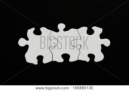 Three Blank Puzzle Pieces Inline On Black Background