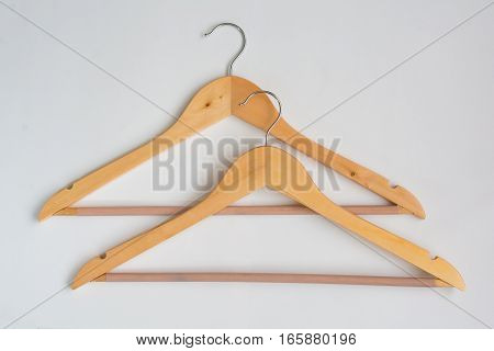 Two Over Lapping Wooden Coat Hangers on white