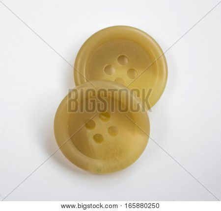Two Cream Colored Plastic Buttons Isolated On White