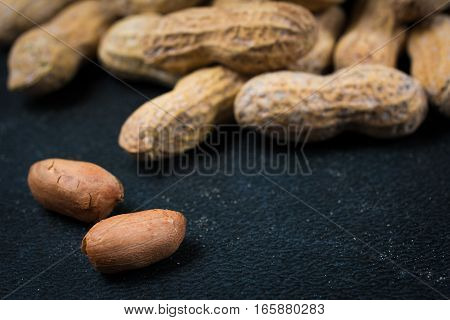 Two Peanuts Without Shells Infront Of Pile Of Peanuts
