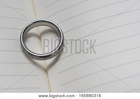 Wedding Ring Band On Book With Heart Shadow Close Up Angled View