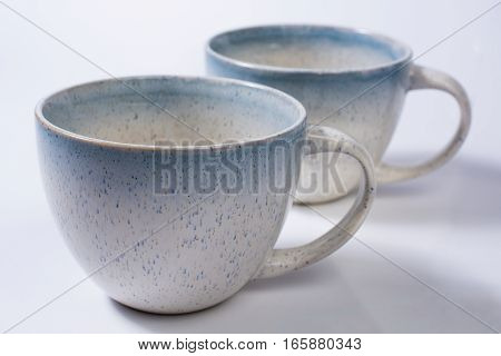 Two Speckled Blue Mugs Isolated On White Close Up