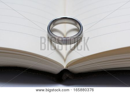Wedding Ring Band on Book Spine with Heart Shadow