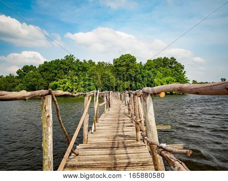wooden bridge with lake, cloud and blue sky background