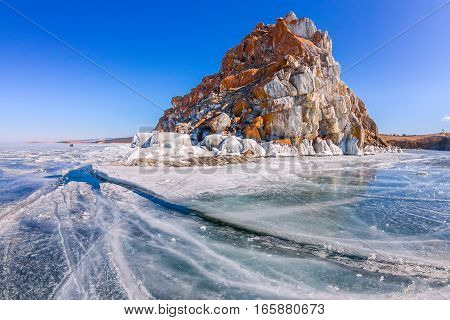 Shaman Rock Or Cape Burhan On Olkhon Island In Winter, Surrounded By The Blue Ice Of Lake Baikal Wit