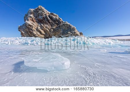 Rock Yador On Olkhon Island In Winter, Surrounded By The Blue Ice Of Lake Baikal With Cracks