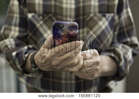 Man in Brown Plaid Shirt Holding iPhone Face On