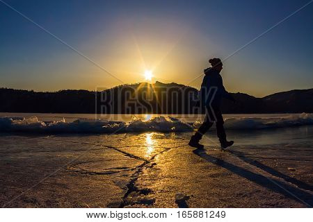 Girl is on the ice of Lake Baikal in the light of the setting sun.