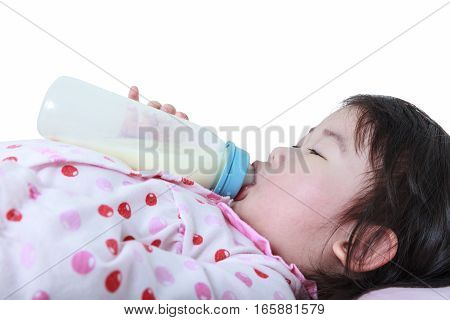 Closeup cute asian girl sucking up milk bottle at bed, on white background. Drinking milk for good health.