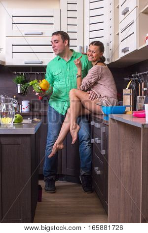 Woman Feeding Food To Man In Kitchen. Family relationship concept.