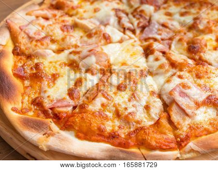 closeup fresh pizza slices on wooden plate