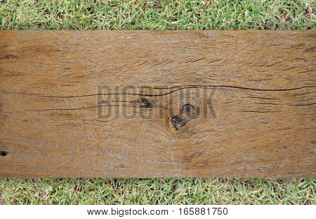 old brown wooden plank on grass for background