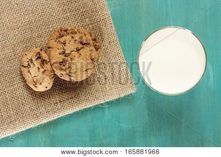 A photo of chocolate chips cookies, shot from above on a vibrant blue background, with a glass of milk. Selective focus