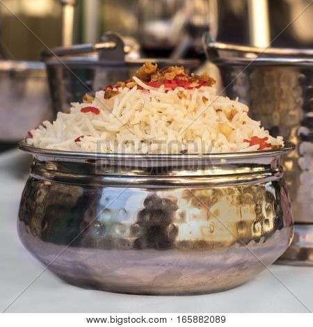 A square photo of a bowl of traditional Indian rice, served in a typical national cuisine restaurant, on a blurred background
