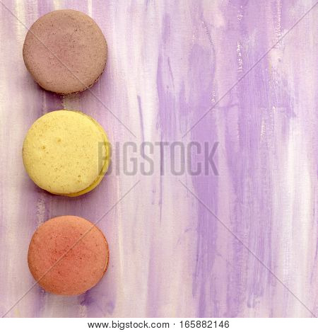 A photo of three macarons, shot from above on a light purple background texture, with copy space