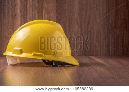 Yellow standard Safety helmet with wood background