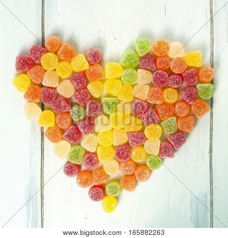 A square photo of a heart made of many vibrant multicolored gum drops, yellow, red, orange, and green, shot from above on light blue wooden background texture, with copyspace