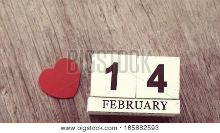 February 14 on wooden cube calendar on blurred wooden table with red heart background vintage style