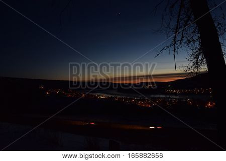 photo of a blue, green, orange sunset with a tree in the forground