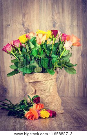 Roses in the sack on wooden background