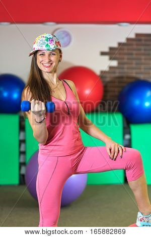 Young Beautiful White Girl In A Pink Sports Suit Does Physical Exercises With Dumbells At The Fitnes