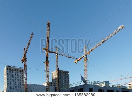 Sihouette of yellow cranes blue sky and high buildings at Hagastaden in Stockholm Sweden