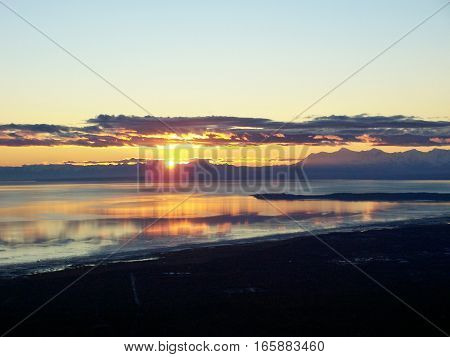 Amazing view of sunset or sunrise reflecting in the ocean from the top of mountain in Anchorage Alaska. Land silhouetted against a colorful morning or evening sky.