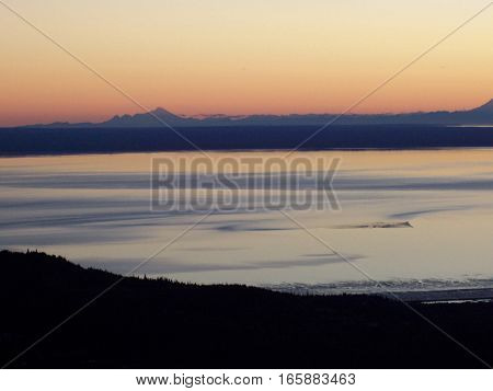 Sunrise or sunset from the top of mountain in Anchorage Alaska. Land silhouetted against a colorful morning sky with orange reflecting on the ocean.