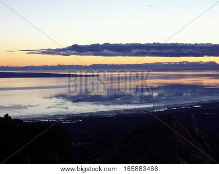 Awesome view of sunrise or sunset from the top of a mountain overlooking the ocean in Anchorage Alaska. Land silhouetted against a colorful sky with clouds reflecting on the water.