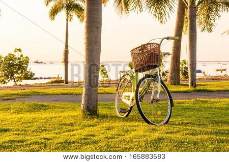 bicycle on the beach with sun light on sunset