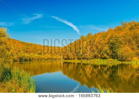 View of a beautiful lake in the autumn forest.