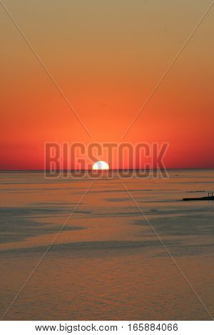 Beautiful sunset on the sea coast. Bathing and fishermen