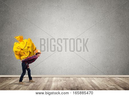 Builder man carrying paper ball on his back