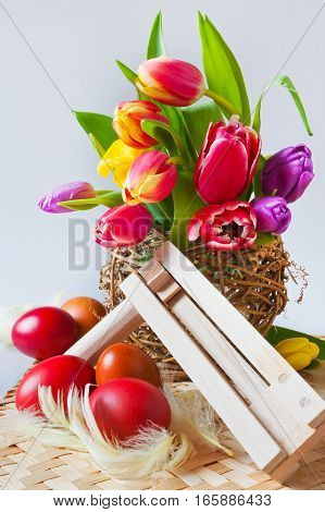 Traditional Czech easter decoration - my handmade painted red and green eggs with tulip flowers and regional music instrument ratchet. Spring easter holiday arrangement.