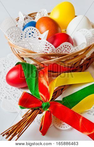 Traditional Czech easter decoration - regional whip with ribbons and decorated eggs in the wicker scuttle. Spring easter holiday arrangement.