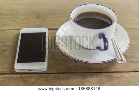 Black coffee in white glass, telephone, on the table brown background