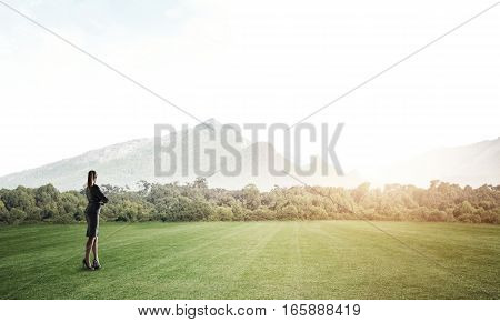 Elegant businesswoman standing on green field and looking ahead