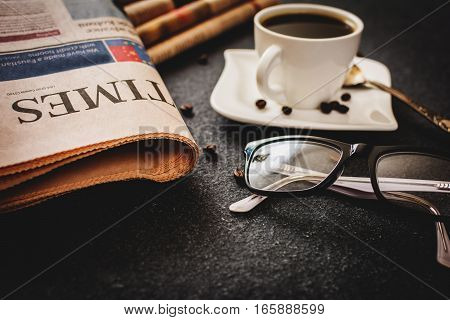 Classes and newspaper and cup of coffee on black stone background